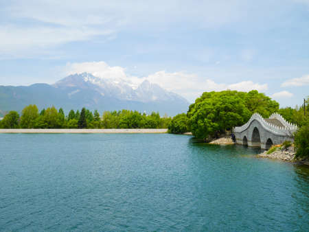 Qingxi reservoir and beautiful bridge with Jade Dragon Snow Mountain in the background. Lijiang, Yunnan, China 免版税图像