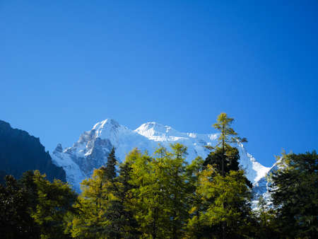 Snow covered mountain peaks in Yading Nature Reserve, Sichuan, China. Snow mountain landscape.