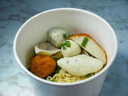 Egg noodle with many kinds of fish balls in takeaway box