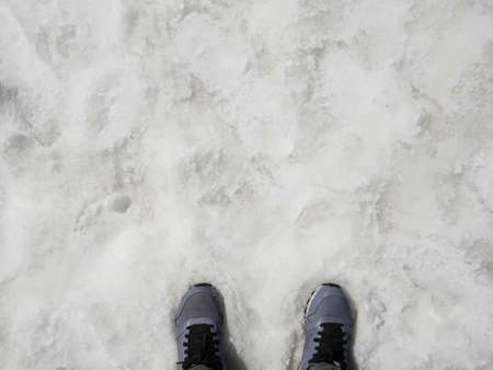Woman with leather sneakers standing in the snow in winter Stock fotó