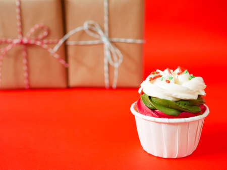 Christmas cupcake with cream cheese frosting and colorful sugar strand sprinkles with presents in the background