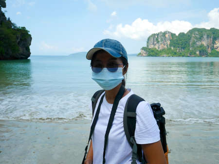 A woman wearing surgical face mask traveling on Railay beach in Thailand