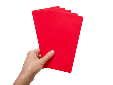 Hand holding red packets or red envelopes isolated on white background. Chinese New Year or Lunar New Year concept.