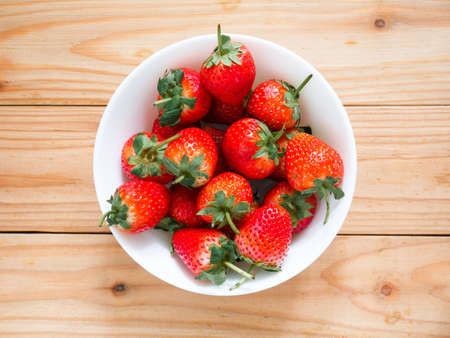 Fresh strawberries in a bowl on wooden table Stock fotó