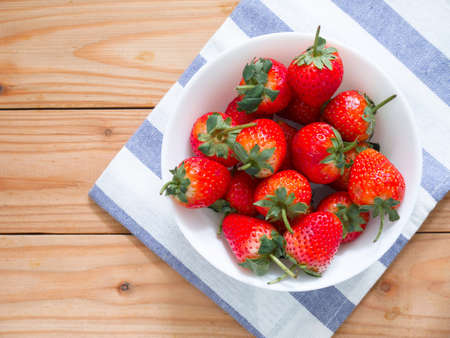 Fresh strawberries in a bowl on wooden table 免版税图像