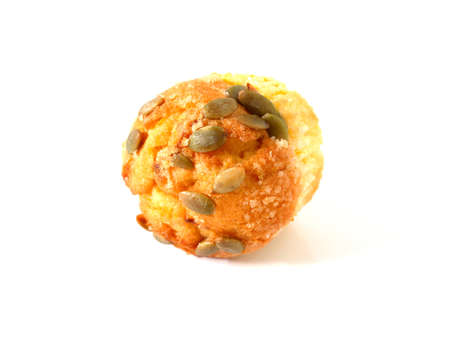 Pumpkin muffin topped with pumpkin seeds isolated on white background