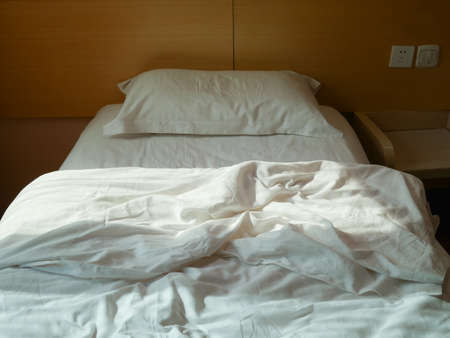 Unmade bed with crumpled duvet, bed sheet and pillow