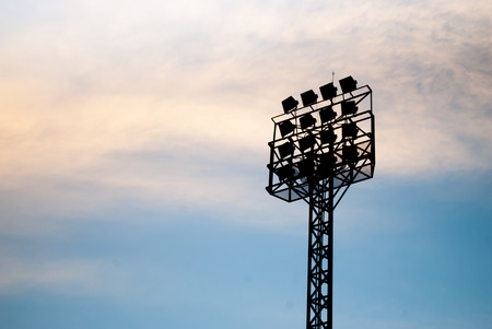 limelight: The silhouette of stadium light stand set against a blue sky with white clouds.