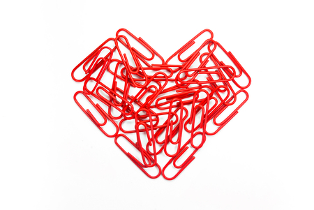 paper clips arranged in heart shape on white background. photo