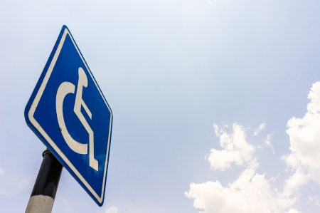Closeup of handicapped parking place sign over blue sky photo