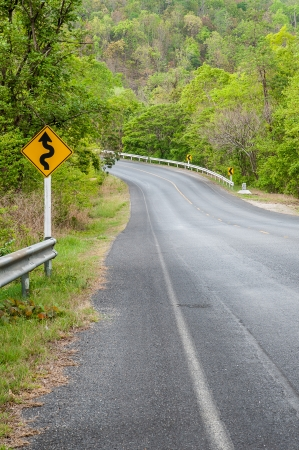 Asphalt winding curve road in green forest at Doi Inthanon National Park photo