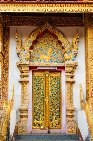 Wooden doors carved into flowers decorated with stained glass, Thai Art.at Wat Phra Phutthabat Tak Pha photo