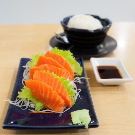 salmon sashimi with garnish, chopsticks,   soy sauce photo