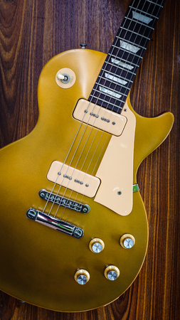 gold top: Vintage gold top single cutaway guitar on wood surface Stock Photo