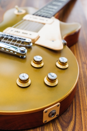 Vintage gold top single cutaway guitar on wood surface 스톡 콘텐츠
