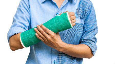broken arm: Green cast on an arm of a women on white background