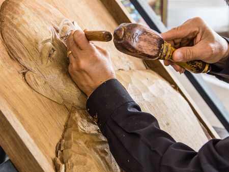 mastery: hands of the craftsman carve a bas-relief