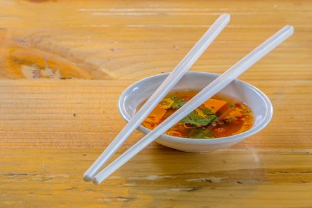 hoisin: Hoisin & Chopsticks - Chopsticks resting on a small white bowl of asian dipping sauce.