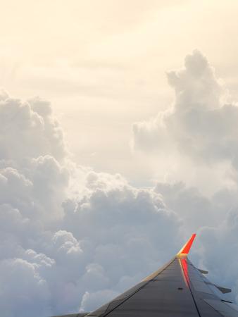 plan éloigné: ciel nuageux et l'aile de l'avion comme on le voit à travers la fenêtre d'un aéronef.