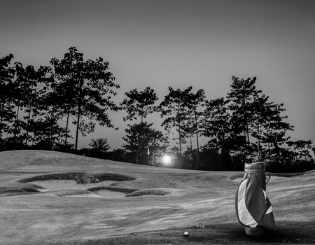 golf course: golf equipment on green and hole as background. vintage tone