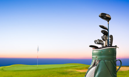 golf clubs: golf equipment and golf bag on green and hole as background. Stock Photo