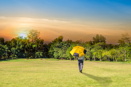 Golfers walking under umbrella on green grass and hole as background.concept go to success.