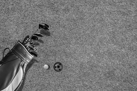 High angle view of golf bag, golf club, gloves and golf ball, with beautiful green lawn floor and golf hole as background.With space to write the text..black &white Stock Photo