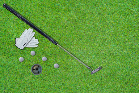 High angle view of Putter golf, golf club, gloves  golf bal and hole with beautiful green lawn floor and golf hole as background With space to write the text.