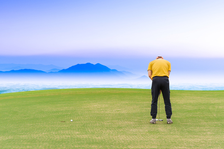 Asian golfer (man) 54 years old Putting golf ball on green  to a hole at golf course sea and blue sky as background