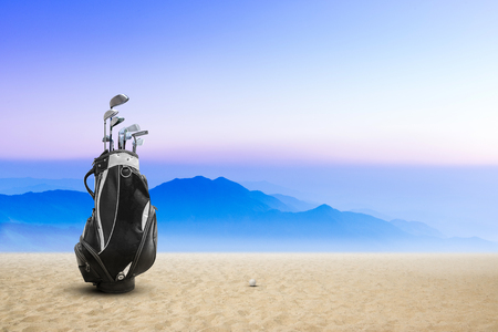 Golf bag golf ball on sand bunker sunset and blue sky as background.Golf shot from sand bunker for win and success concept.