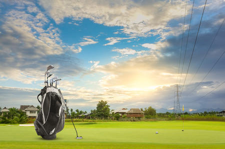 Golf equipment and golf bag , putter, ball on green sunset as background Stok Fotoğraf