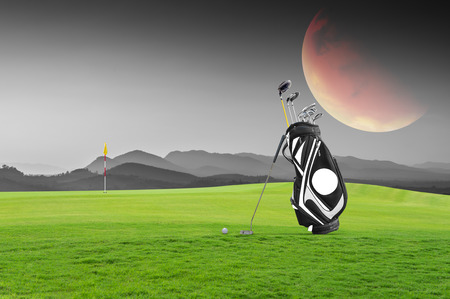 Golf equipment and golf bag , putter, ball on green at golf course the moon as  background.