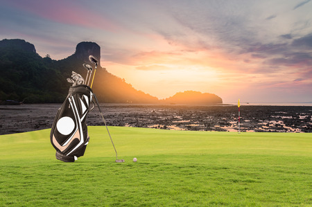 Golf equipment and golf bag , putter, ball on green at golf course sunset as  background. Stok Fotoğraf