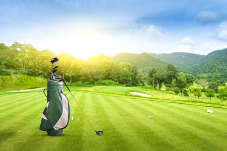 Golfuitrusting en golftas golfbal op groen bij de blauwe hemel van de golfbaanzonsondergang als achtergrond.