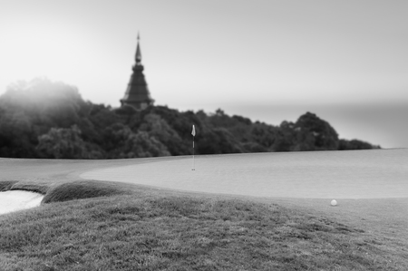 Golf ball on green  flag and golf hole as background.black and white.