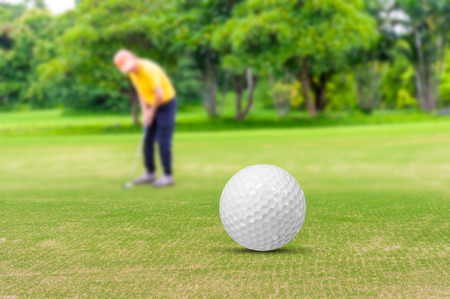 Golf ball on green and golfer background.