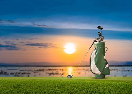 Golf bag, ball, putter and driver  (wood no 1) on green sunset as background.