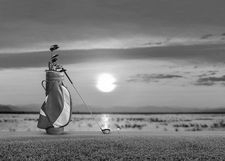 Golf bag, ball, putter and driver  (wood no 1) on green sunset as background. black and white. Stock Photo