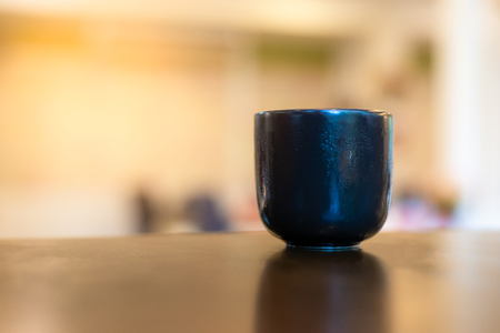 Black Chinese Ceramic Mug on the wood table .