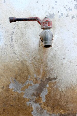 Old rusted tap on wall Stock Photo - 14496803