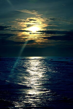 Decline over dark blue by sea, a solar beam making the way through clouds Stock Photo - 5489613