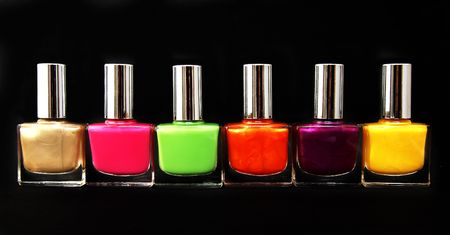 Colour vials of nail polish on a black background