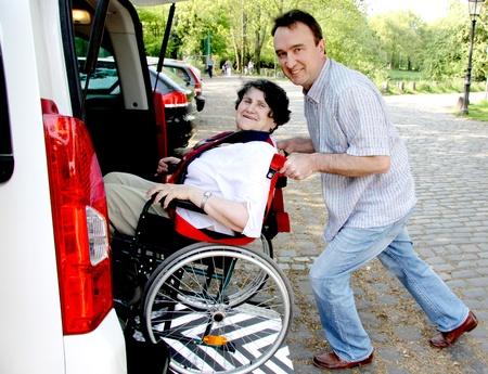 handicap: Giovane uomo donna senior che assistenza in sedia a rotelle  Archivio Fotografico