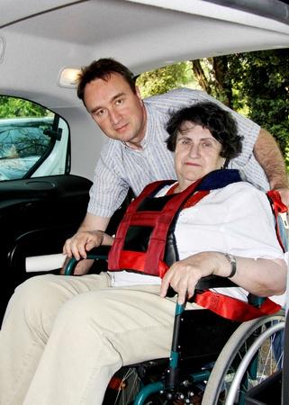 persona en silla de ruedas: Joven para ayudar a la mujer senior en silla de ruedas  Foto de archivo