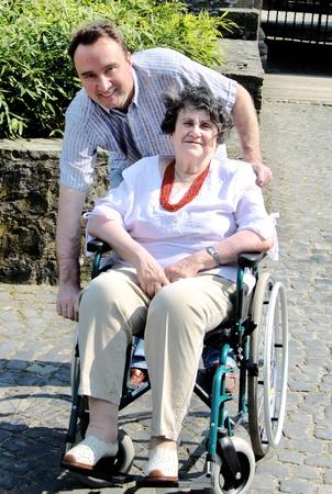 handicap people: Joven para ayudar a la mujer senior en silla de ruedas  Foto de archivo