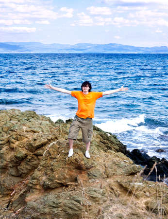 The young man costs(stands) on a stone at the sea having stretched hands.  photo