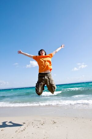 The young man jumps on sand at the sea Stock Photo - 13520427