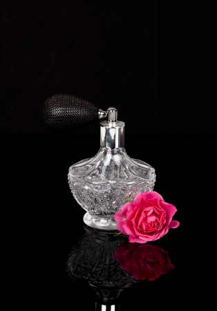 Luxurious perfume bottle atomizer with flower blossom isolated on black background.