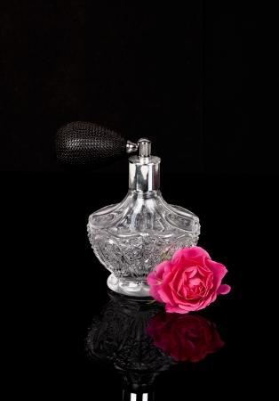 parfum: Luxurious perfume bottle atomizer with flower blossom isolated on black background.