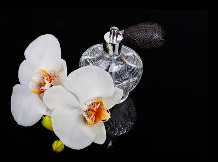 atomizer: Luxurious perfume bottle atomizer with flower blossom isolated on black background. Stock Photo
